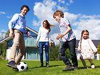 SPARDA Immobilien GmbH - Familie spielt im Garten Fussball / SPARDA Immobilien GmbH