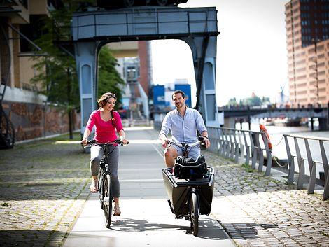Eine Frau und ein Mann fahren Fahrrad in der Sonne