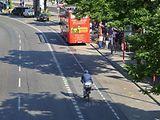 Ein Radfahrer fährt auf dem Fahrradweg an den Landungsbrücken. Ein roter Doppeldeckerbus steht an der Bushaltestelle.