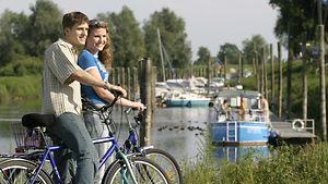 Mann und Frau mit Fahrrädern vor kleinem Binnenhafen / Lüneburg Marketing
