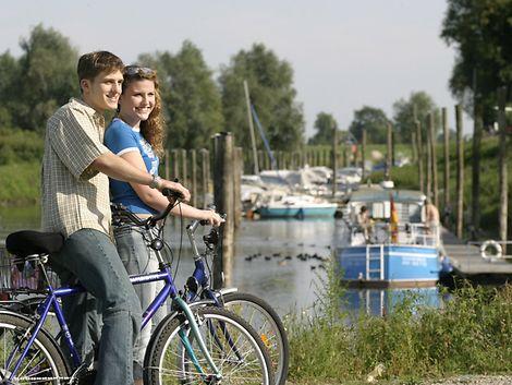 Mann und Frau mit Fahrrädern vor kleinem Binnenhafen