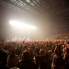 Konzertsaal mit Bühne, Band und feiernden Konzertbesuchern