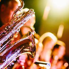 Saxophon und andere Blechbläser vor Bühnenbeleuchtung