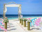 Tisch und zwei Stühle mit weißen Tüchern und Rosenbogen am Strand vor türkisblauem Wasser