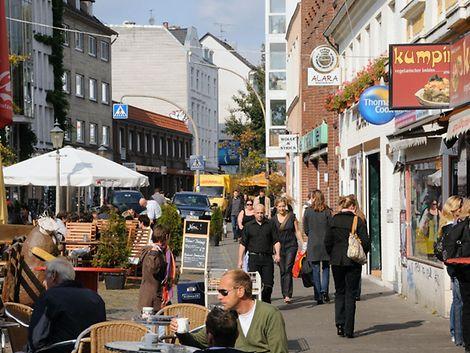 Menschen sitzen in der Sonne in einem Straßencafé auf dem Alma-Wartenberg-Platz in Ottensen / Christoph Bellin / bildarchiv-hamburg.de