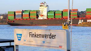Schild des Fähranlegers Finkenwerder mit einem Containerschiff im Hintergrund / Christoph Bellin / bildarchiv-hamburg.de