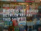 ein Schaufenster mit dem englischen Text: Where is the border between art and this shop?