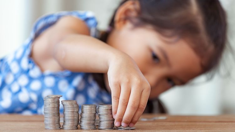 asian little girl playing with coins making stacks of money