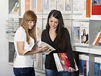 Eine Mitarbeiterin des Berufsinformationszentrums zeigt einer jungen Frau ein Magazin